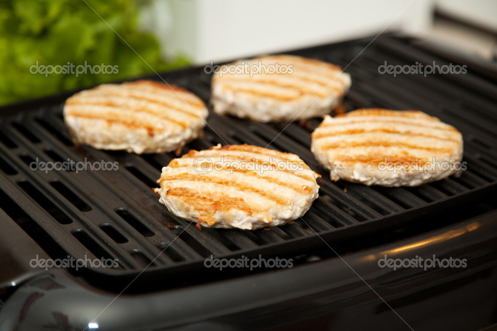 Healthy, low-fat turkey burgers cooking on indoor grill.    Stock Photo #6804178