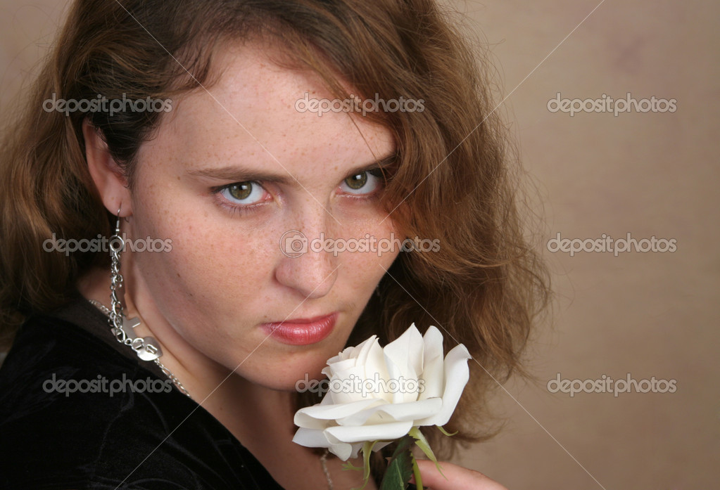 A beautiful red haired young woman posing with a white rose.  Stock Photo #6804266
