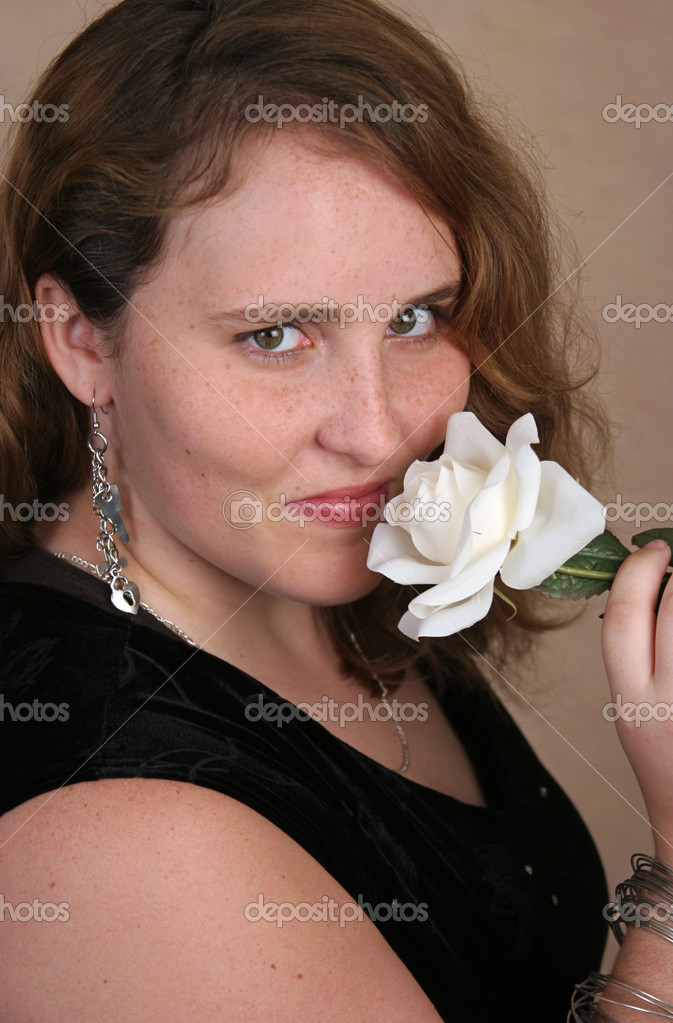 A beautiful young woman sniffing a white rose.  Stock Photo #6804303