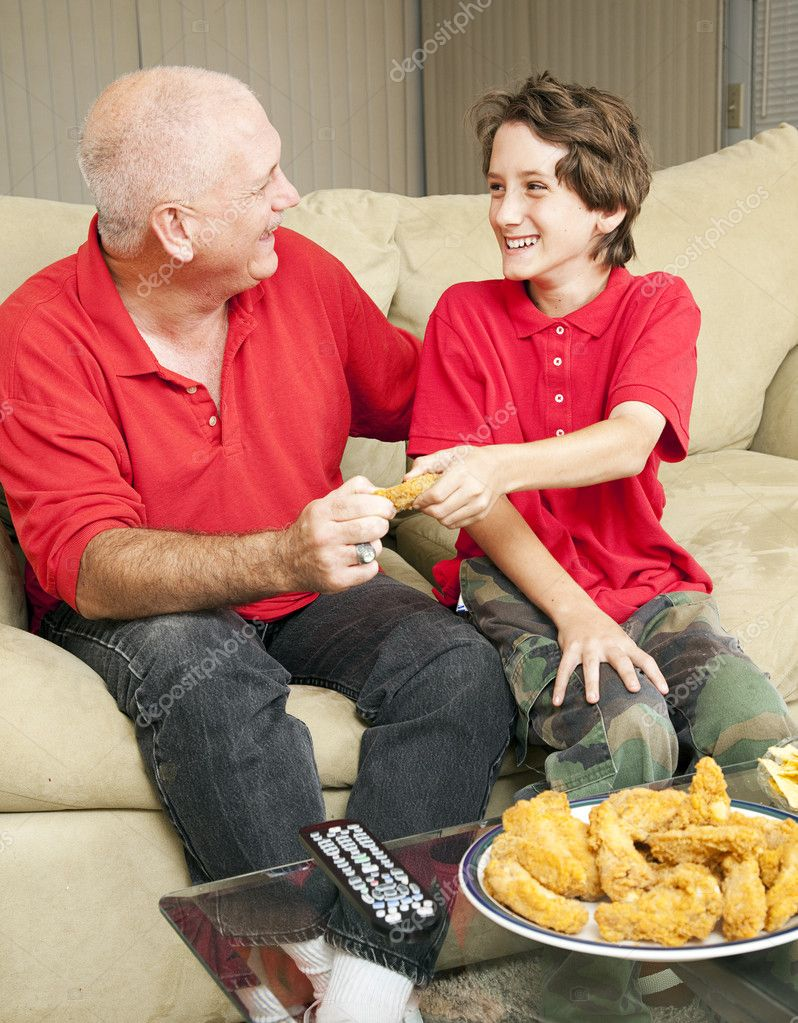 Little boy and his father watching football and fighting over a fried chicken wing.    Stock Photo #6804777
