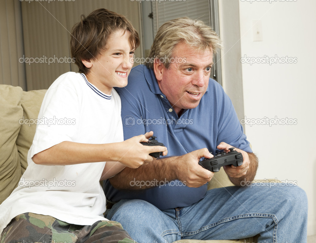 Father or uncle playing video games with a little boy - his son or nephew.    Stock Photo #6804793
