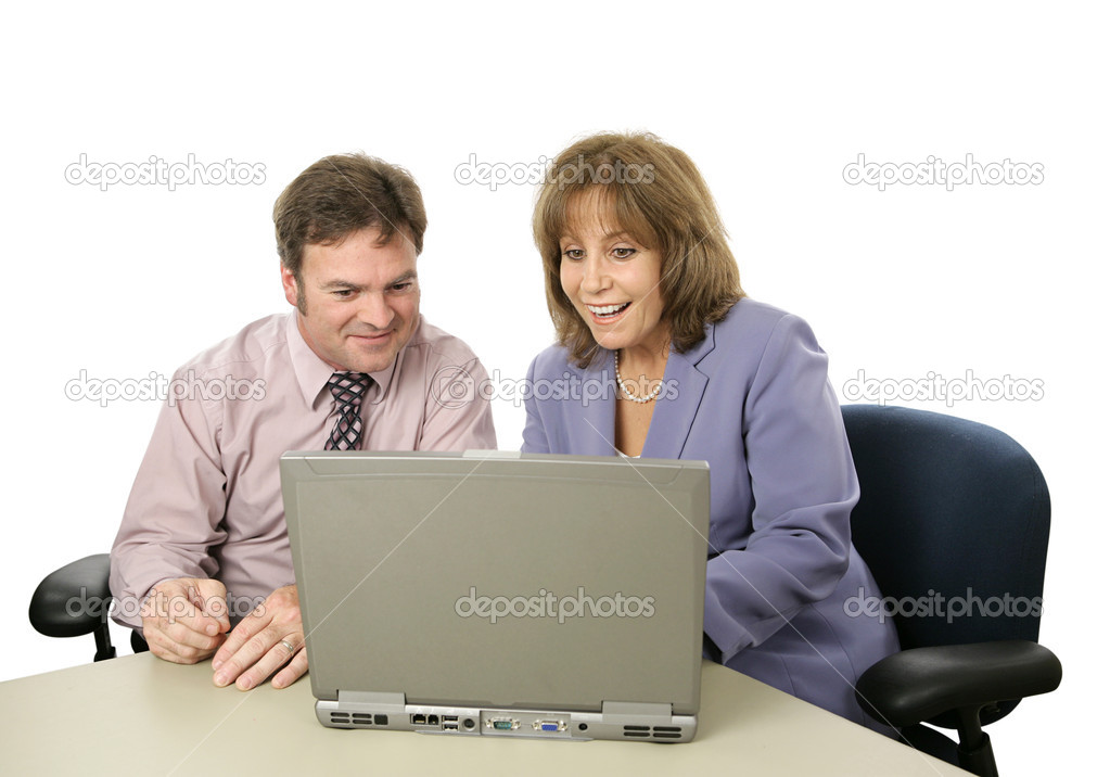 A male-female business team happy about what they see on the computer.  Isolated.  Stock Photo #6805104