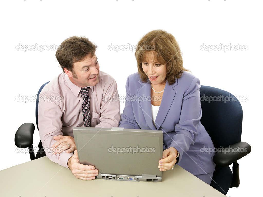 A male-female business team.  He is showing her something surprising on his laptop.    Stock Photo #6805105