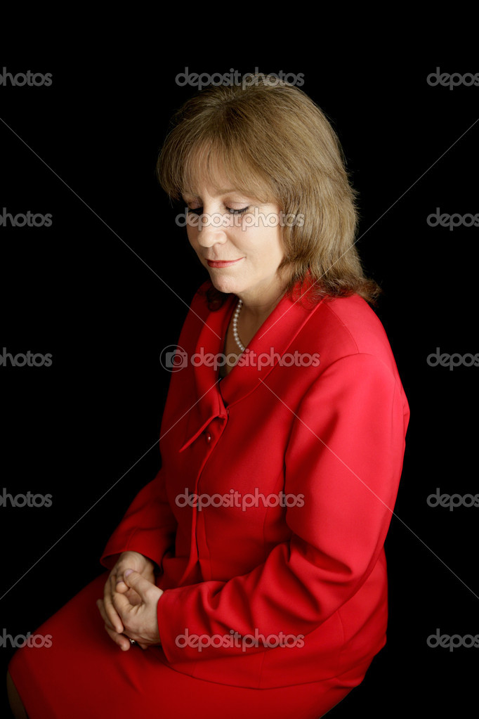 A pretty business woman in a red suit, alone with her thoughts.  Black background. — Photo #6805182
