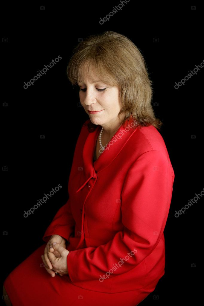 A pretty business woman in a red suit, alone with her thoughts.  Black background. — Lizenzfreies Foto #6805182