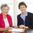 Stock Photo: Senior Woman Signing Paperwork