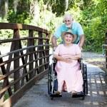 Senior Pushes Wife in Wheelchair — Stock Photo
