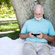 Stock Photo: Senior Texts on Smart Phone