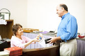 Disabled Clerk Serves Customer — Stock Photo