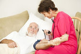 Home Health Nurse Takes Blood Pressure — Stock Photo