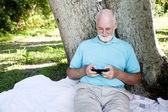Textos Senior en teléfonos inteligentes — Foto de Stock