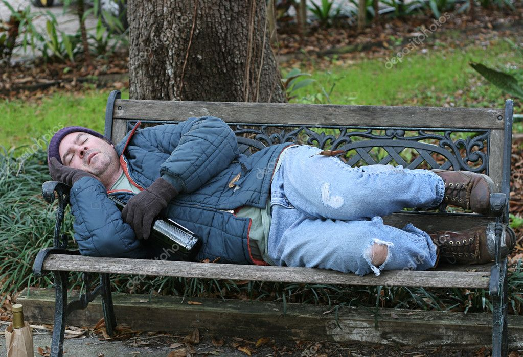 A full view of a homeless man asleep on a park bench with his wine bottle. — Stock Photo #6812897