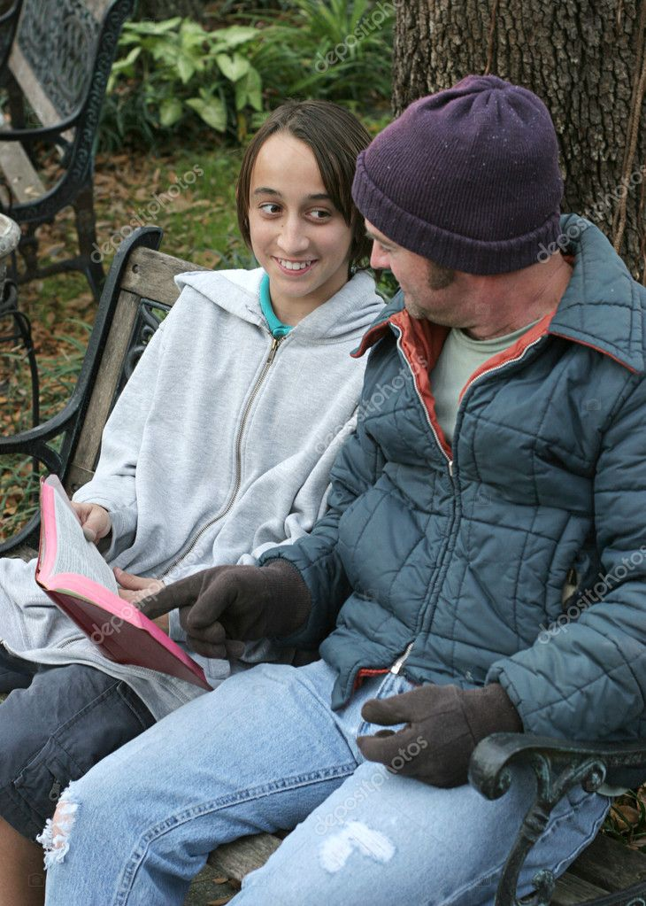 A teenaged volunteer explaining the bible to a homeless man.  Stock Photo #6812901