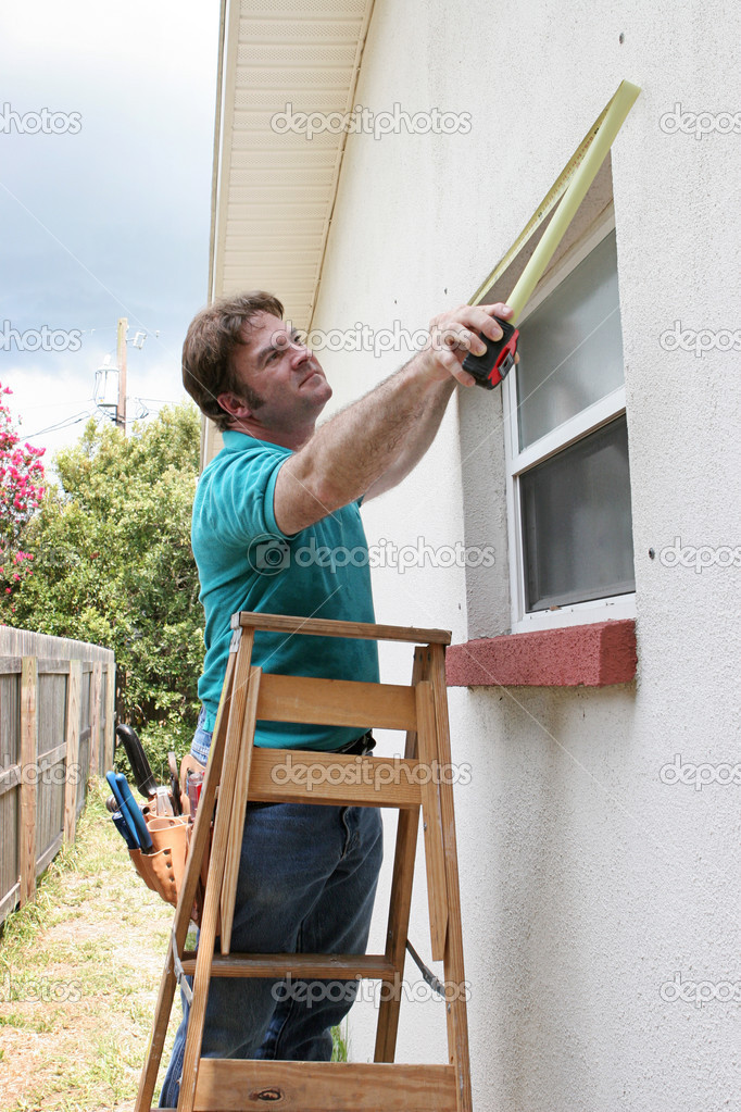 A carpenter or handyman measuring windows for storm shutters.   — Stock Photo #6813504