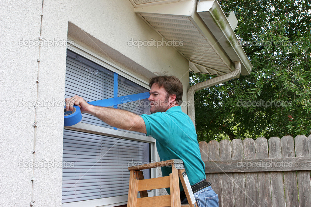 A man taping up his windows to protect from broken glass during a hurricane. — Stock Photo #6813505