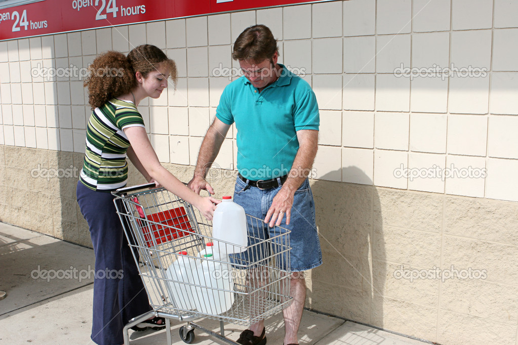 A father and daughter shopping for hurricane supplies.  Their cart is full of water jugs.  Image also appropriate for recycling. — Stock Photo #6813512