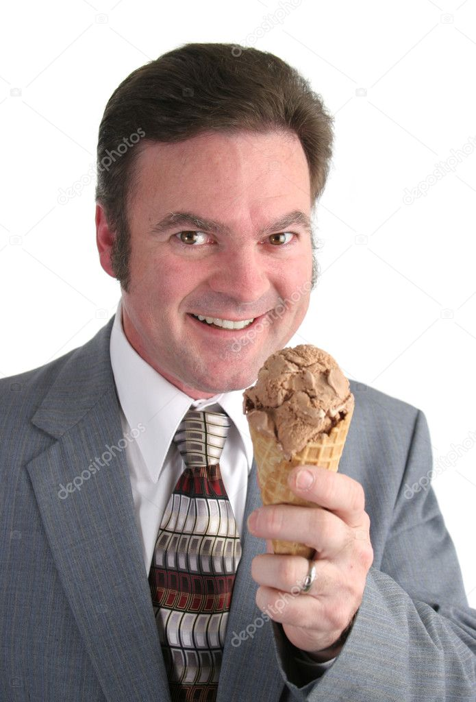A businessman smiling as he gets ready to eat a chocolate ice cream cone.  Lizenzfreies Foto #6813786