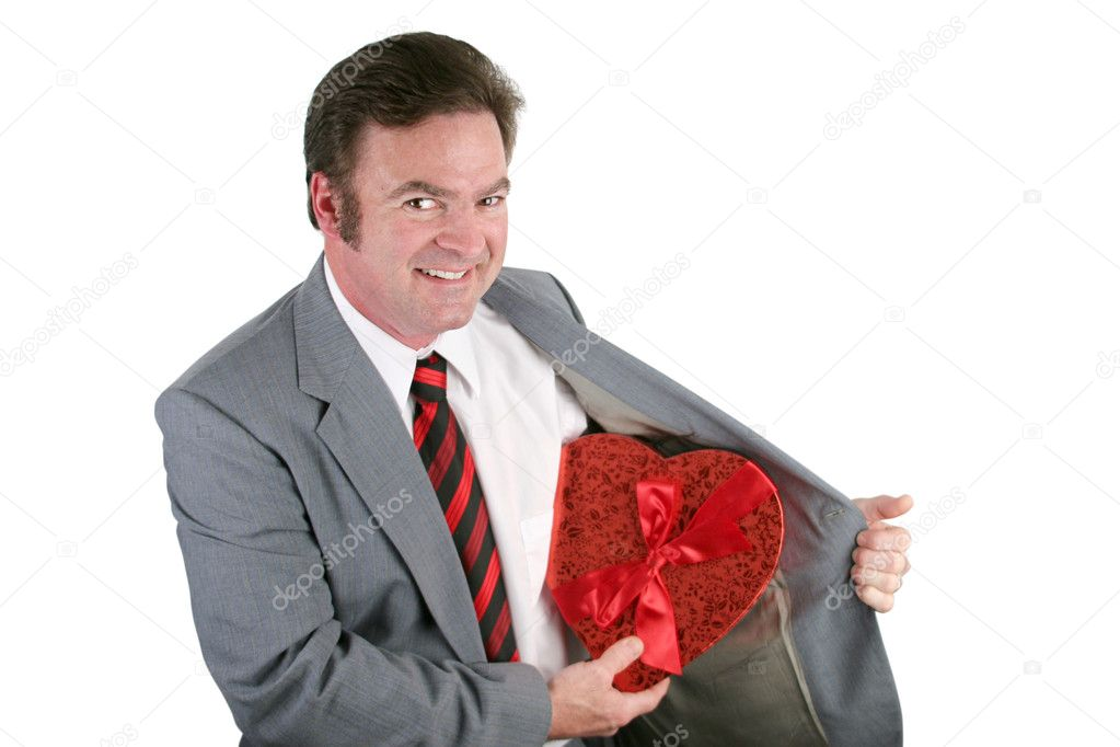 A man in a business suit revealing a box of Valentines chocolates hidden in his jacket.  Isolated on white — Stock Photo #6813817
