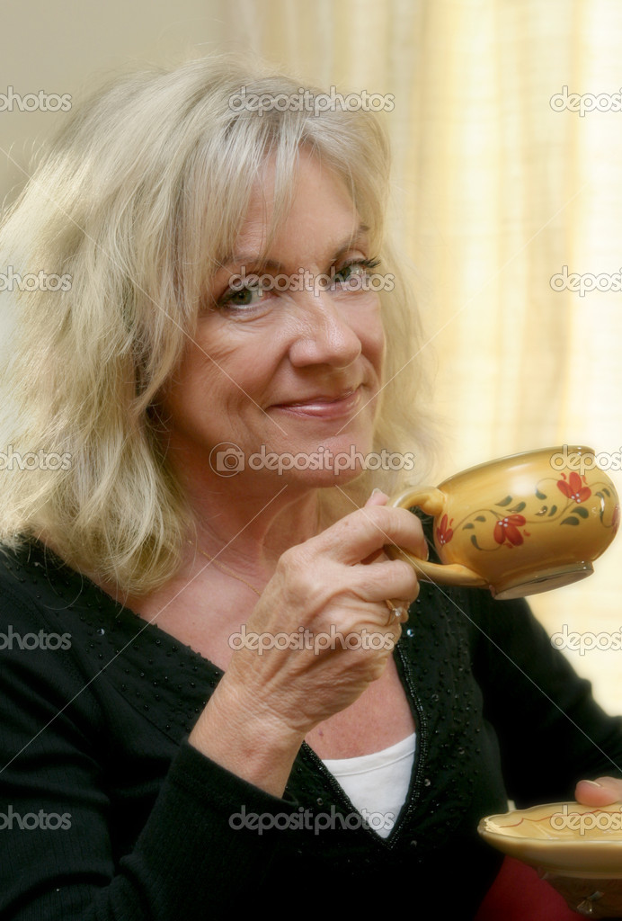 A beautiful mature woman enjoying a cup of coffee.  Soft focus applied. — Stock Photo #6813942