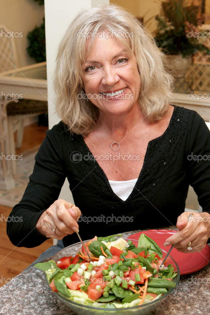A beautiful woman in her fifties staying fit by eating healthy.  Stock Photo #6813952