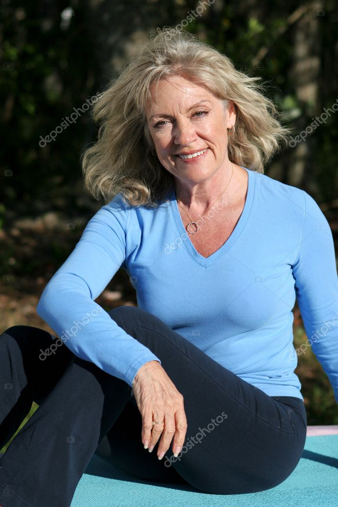 A beautiful fifty year old woman relaxing after doing yoga.  Stock Photo #6813978