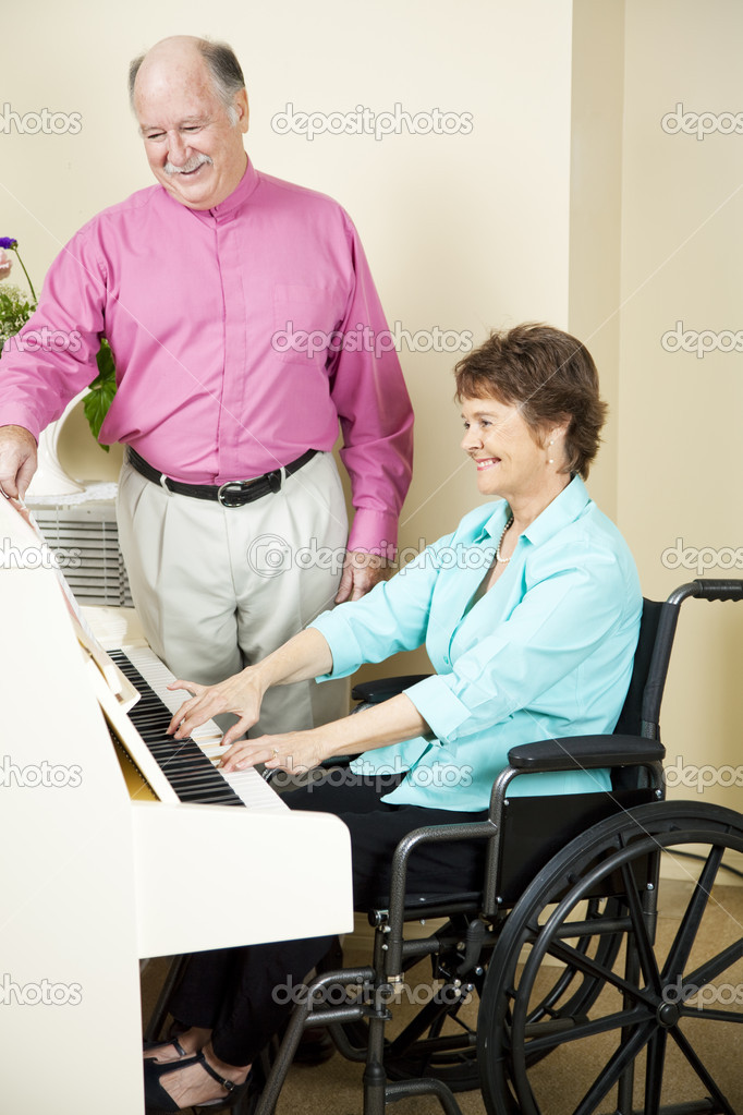 Disabled woman plays piano while an assistant turns pages for her.   — Stock Photo #6815532