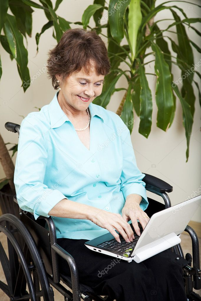 Disabled businesswoman using a tiny netbook computer.   Stock Photo #6815543