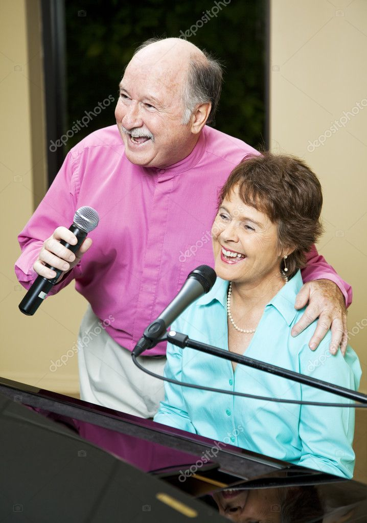 Senior couple performs.  They both sing while she plays piano.   — Stock Photo #6815666
