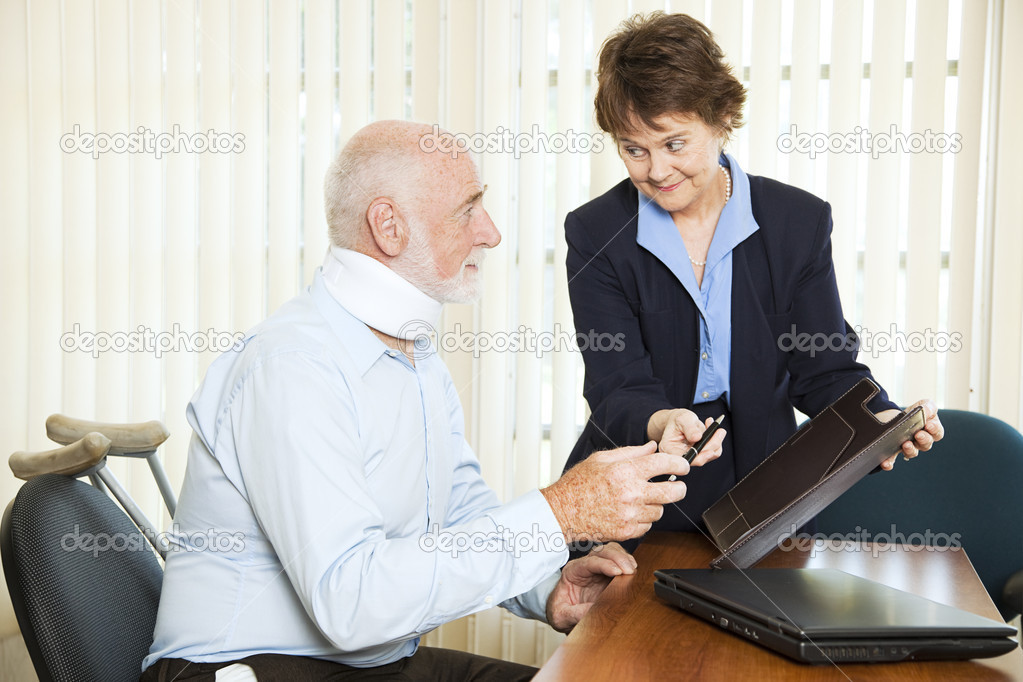 Injured man signing a settlement offer from the attorney.    Stock Photo #6815945