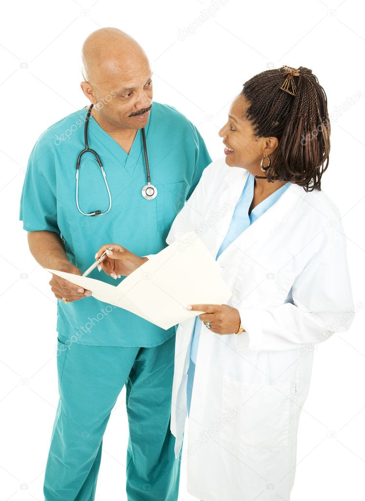 Male and female doctors going over a patient's medical chart.  Isolated on white. — Stock Photo #6816244