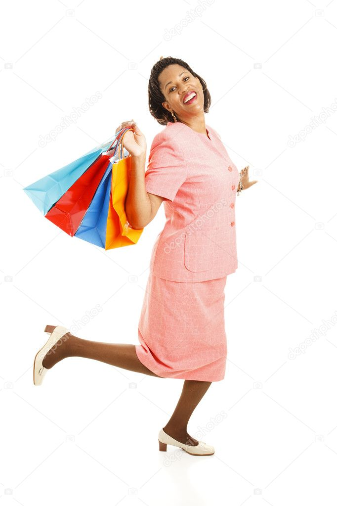 Happy african-american woman skipping along with her shoppping bags.  Full body isolated on white.   — Stock Photo #6816288