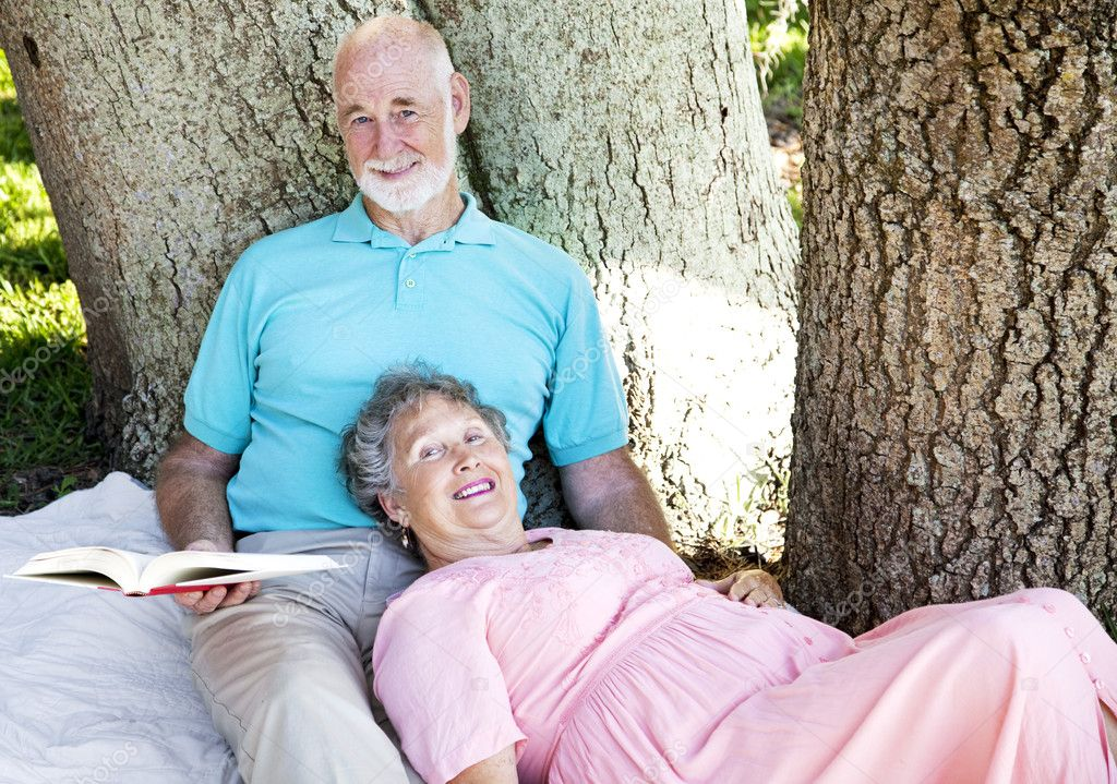 Senior couple reading together outdoors in the park.   — Stock Photo #6817124