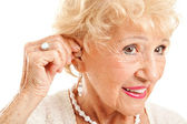 Senior Woman Inserts Hearing Aid — Stockfoto