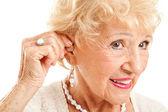 Senior Woman Inserts Hearing Aid — Stock Photo