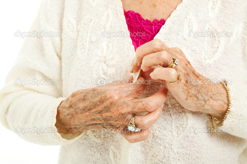 Senior woman's arthritic hands struggling to button her sweater.   — Stockfoto #7292082