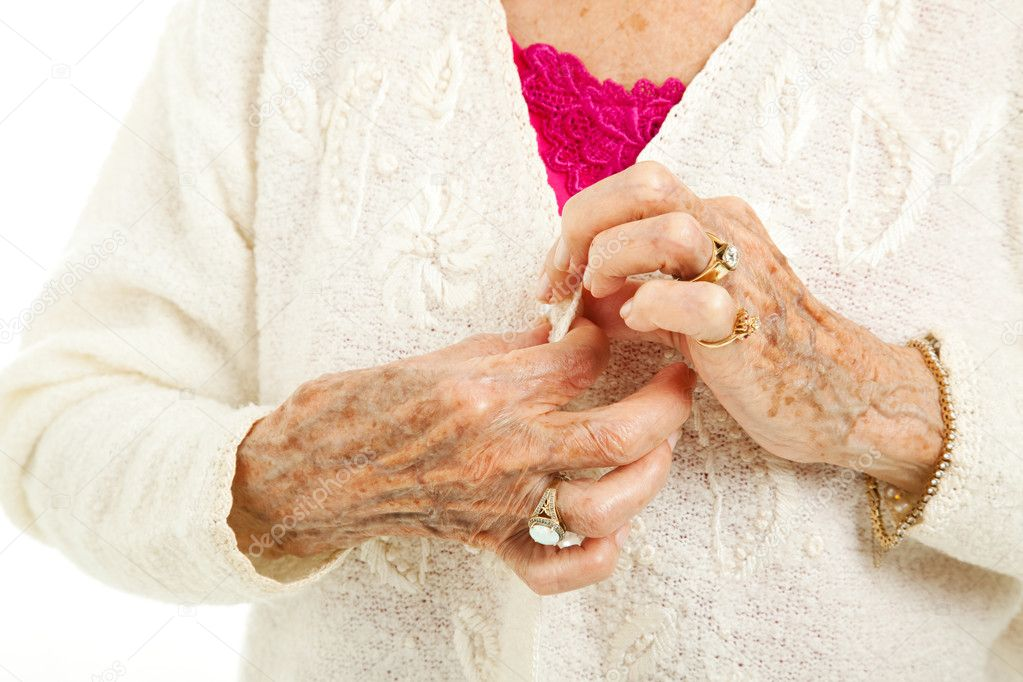 Senior woman's arthritic hands struggling to button her sweater.   — Stock fotografie #7292082