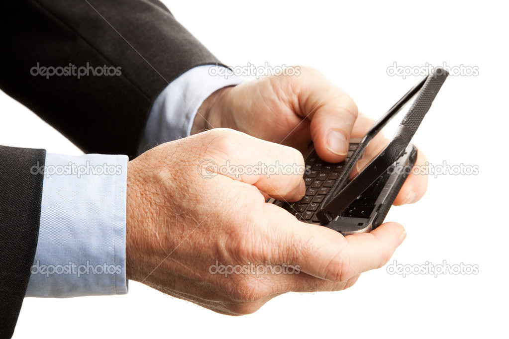 Closeup of a businessman's hands, using his smart phone to text.  Shallow depth of field with focus on the hand and part of the keyboard closest to the camera.   Stock Photo #7293502