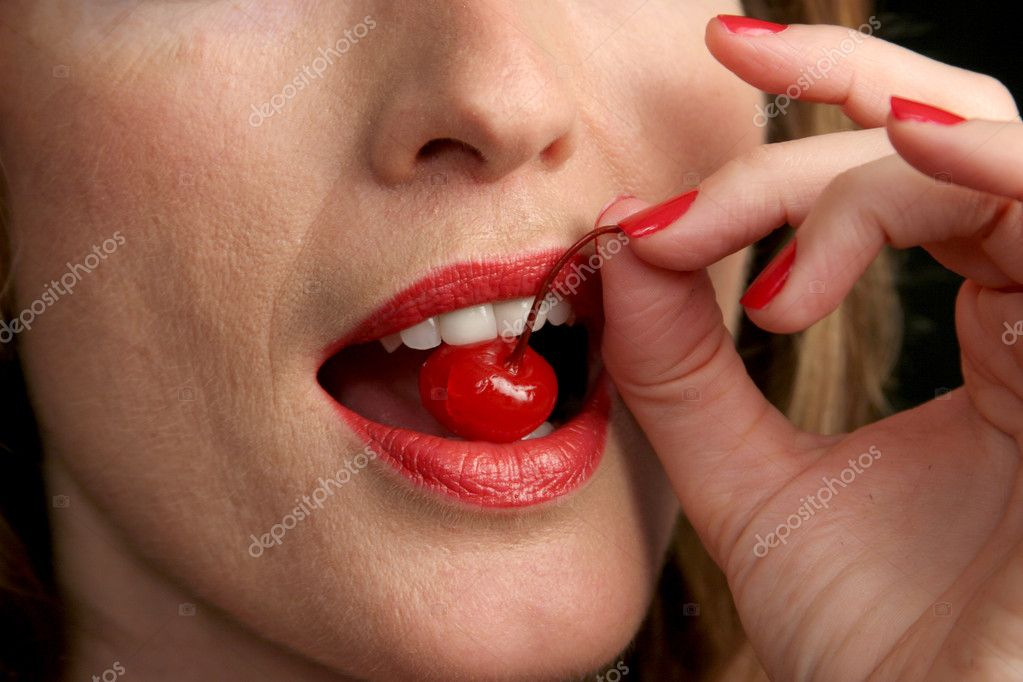 A closeup of red lips and white teeth biting into a bright red cherry. — Stock Photo #7315057