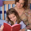A mother and daughter reading bedtime stories together — Stock Photo