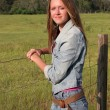 Stock Photo: Country Girl by Fence 1