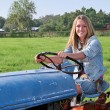 Girl Driving Tractor - Stock Photo