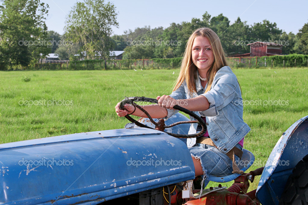 A beautiful farmer's daughter driving a tractor through a green field. — Stock Photo #7322215