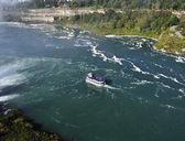 A boat in a river next to Niagara falls — Stock Photo