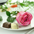 Romantic dinner with rose on a plate - Stock Photo