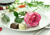 Romantic dinner with rose on a plate — Stock Photo