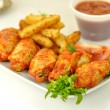 Hot chicken wings with fried potatoes — Stock Photo