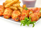 Hot chicken wings with fried potatoes and sauce — Stock Photo