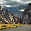 Road to mountains and dramatic sky — Stock Photo