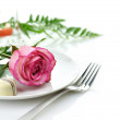 Rose and candy on a plate — Stock Photo
