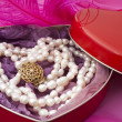 Pearls in a heart-shaped box on a pink background — Stock Photo #7382050